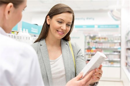 Pharmacist recommending product to customer in pharmacy Stock Photo - Premium Royalty-Free, Code: 6113-08088418