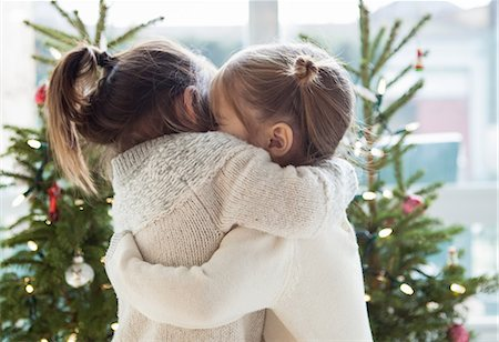 Girls hugging in front of Christmas trees Stock Photo - Premium Royalty-Free, Code: 6113-08088524