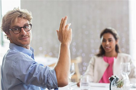Man gesturing for service at restaurant table Stock Photo - Premium Royalty-Free, Code: 6113-08171151