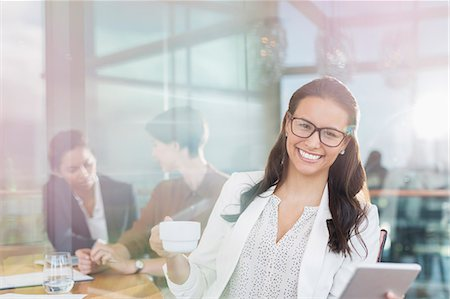 Portrait confident businesswoman with digital tablet and coffee in office Stock Photo - Premium Royalty-Free, Code: 6113-08171241