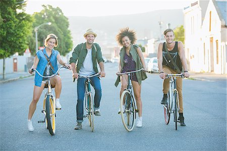 Portrait smiling friends sitting on bicycles on road Stock Photo - Premium Royalty-Free, Code: 6113-08171268