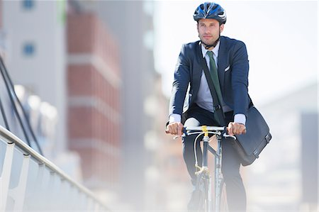 Businessman in suit and helmet riding bicycle in city Foto de stock - Royalty Free Premium, Número: 6113-08171287