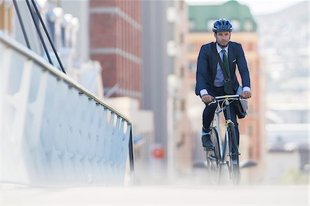 security - Businessman in suit and helmet riding bicycle in city Stock Photo - Premium Royalty-Free, Code: 6113-08171291