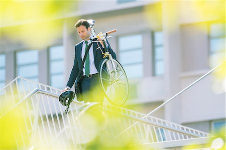 Businessman in suit carrying bicycle in city Foto de stock - Royalty Free Premium, Número: 6113-08171298