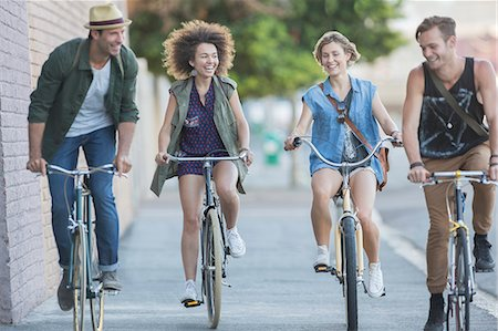 front - Friends riding bicycles on urban sidewalk Stock Photo - Premium Royalty-Free, Code: 6113-08171360
