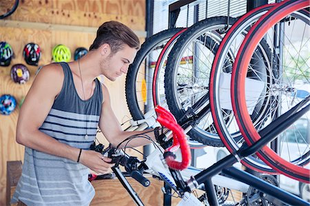 Young man examining bicycle on rack in bicycle shop Stock Photo - Premium Royalty-Free, Code: 6113-08171368