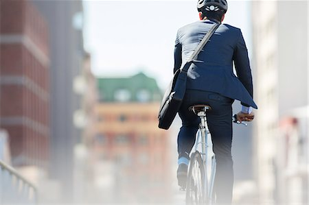 security - Businessman in suit and helmet riding bicycle in city Stock Photo - Premium Royalty-Free, Code: 6113-08171303