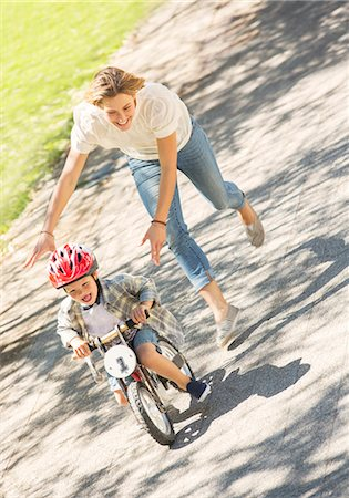 Mother pushing son with helmet on bicycle in sunny park Stock Photo - Premium Royalty-Free, Code: 6113-08171305