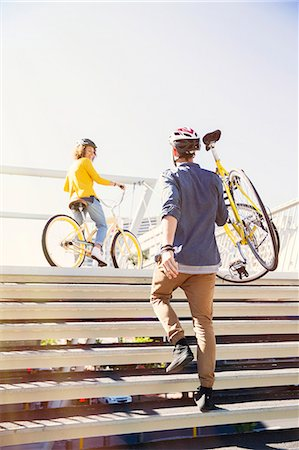 Man in helmet carrying bicycle up urban stairs Stock Photo - Premium Royalty-Free, Code: 6113-08171315