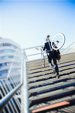 Businessman carrying bicycle up urban stairs under sunny blue sky Stock Photo - Premium Royalty-Free, Code: 6113-08171319