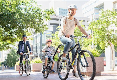 Mother and son in helmets riding tandem bicycle in urban park Foto de stock - Royalty Free Premium, Número: 6113-08171327