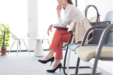 Businesswoman waiting with legs crossed in lobby Stock Photo - Premium Royalty-Free, Code: 6113-08171467
