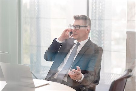 Businessman talking on cell phone gesturing in office Stock Photo - Premium Royalty-Free, Code: 6113-08171435