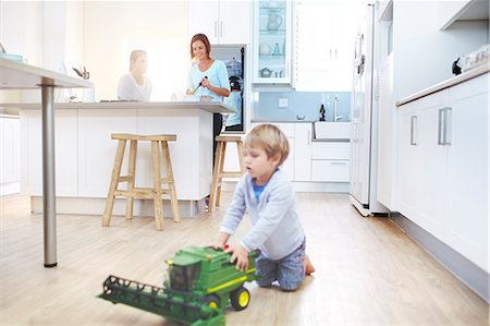 Women cooking in kitchen while boy plays with toy tractor on floor Stock Photo - Premium Royalty-Free, Code: 6113-08171503