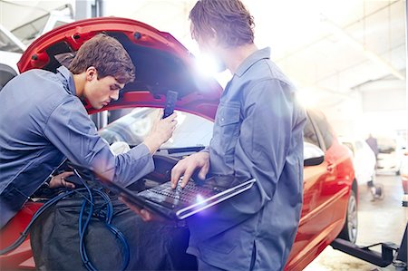 Mechanics with laptop working on car engine in auto repair shop Stock Photo - Premium Royalty-Free, Code: 6113-08184354