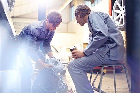 Mechanics examining engine part in auto repair shop Stock Photo - Premium Royalty-Free, Code: 6113-08184356