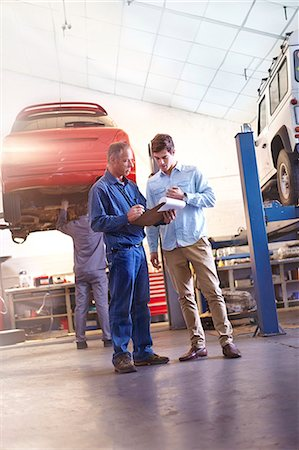 services - Mechanic with clipboard talking to customer in auto repair shop Stock Photo - Premium Royalty-Free, Code: 6113-08184358