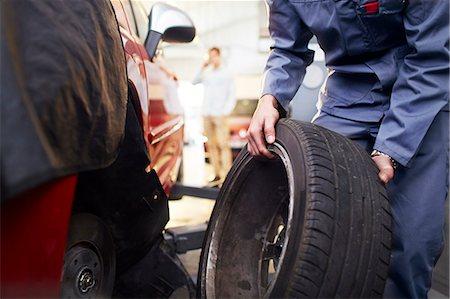 Mechanic replacing tire in auto repair shop Stock Photo - Premium Royalty-Free, Code: 6113-08184361