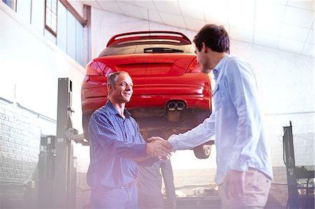Mechanic and customer handshaking in auto repair shop Stock Photo - Premium Royalty-Free, Code: 6113-08184362