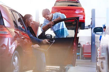 Mechanic with laptop talking to customer at car in auto repair shop Stock Photo - Premium Royalty-Free, Code: 6113-08184369