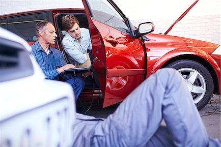 Mechanics with laptop talking at car in auto repair shop Stock Photo - Premium Royalty-Free, Code: 6113-08184372