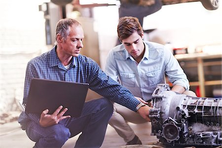Mechanic with laptop and customer examining engine in auto repair shop Stock Photo - Premium Royalty-Free, Code: 6113-08184376