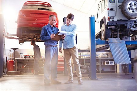 services - Mechanic with clipboard talking in auto repair shop Stock Photo - Premium Royalty-Free, Code: 6113-08184386