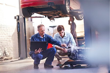 Mechanic and customer with laptop examining engine in auto repair shop Stock Photo - Premium Royalty-Free, Code: 6113-08184390