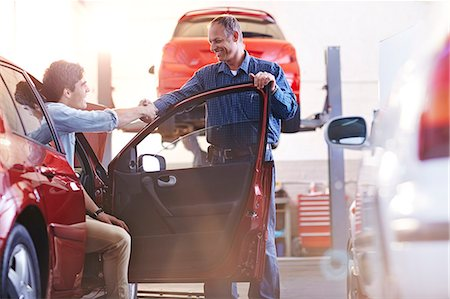 Mechanic and customer in car handshaking in auto repair shop Stock Photo - Premium Royalty-Free, Code: 6113-08184392