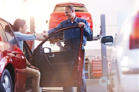 Mechanic and customer in car handshaking in auto repair shop Stock Photo - Premium Royalty-Free, Code: 6113-08184392