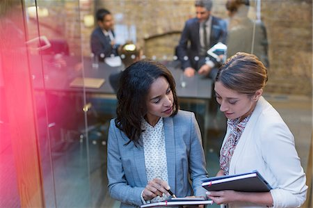 Businesswomen talking outside conference room meeting Stock Photo - Premium Royalty-Free, Code: 6113-08184300