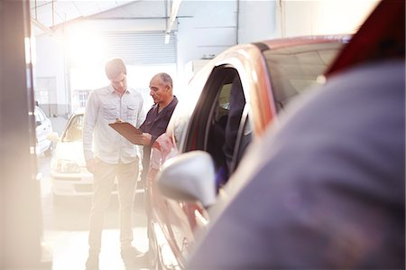 Mechanic with clipboard talking to customer in auto repair shop Stock Photo - Premium Royalty-Free, Code: 6113-08184334