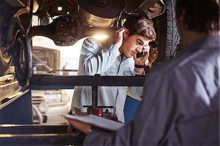 Mechanic and customer talking on cell phone under car Stock Photo - Premium Royalty-Free, Code: 6113-08184335