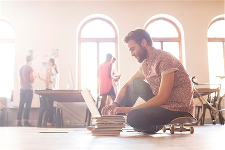 piles of work - Casual businessman working at laptop from skateboard Stock Photo - Premium Royalty-Free, Code: 6113-08105341