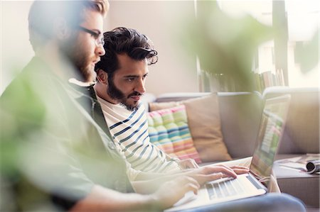 Casual businessmen working at laptop on sofa in office Stock Photo - Premium Royalty-Free, Code: 6113-08105349