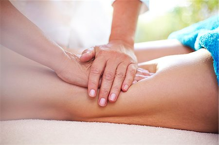 Masseuse rubbing woman's legs Stock Photo - Premium Royalty-Free, Code: 6113-08105451