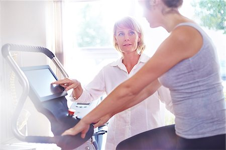 fitness   mature woman - Physical therapy guiding woman on stationary bike Stock Photo - Premium Royalty-Free, Code: 6113-08105477