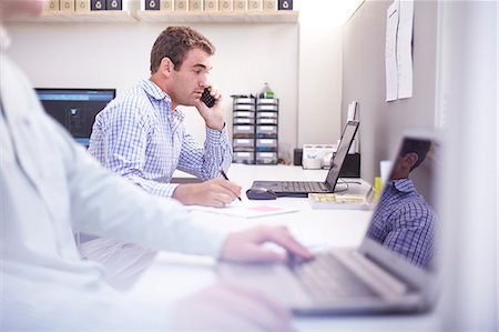 Architect talking on cell phone and working at laptop in office Stock Photo - Premium Royalty-Free, Code: 6113-08105521