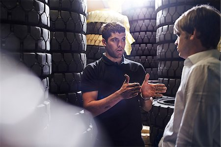 Mechanic and customer talking near stacked tires Stock Photo - Premium Royalty-Free, Code: 6113-08220186