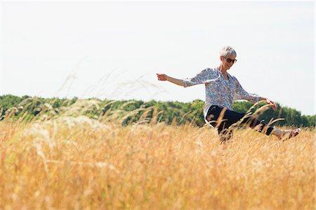 Playful senior woman dancing in sunny rural field Stock Photo - Premium Royalty-Free, Code: 6113-08220247