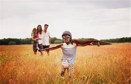 Playful boy with wings in aviator's cap and flying goggles in field Stock Photo - Premium Royalty-Free, Code: 6113-08220216