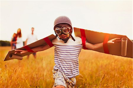Boy with wings in aviator's cap and flying goggles in field Stock Photo - Premium Royalty-Free, Code: 6113-08220237