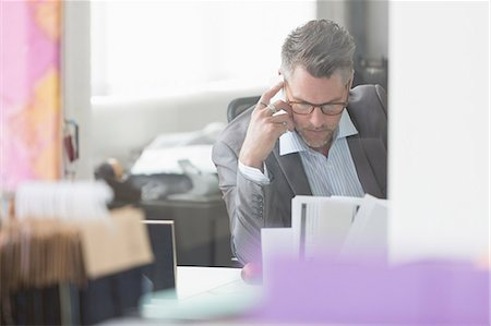 Focused businessman reviewing paperwork at desk in office Stock Photo - Premium Royalty-Free, Code: 6113-08220362