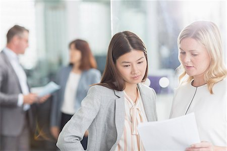 east asian - Businesswomen discussing paperwork in office Stock Photo - Premium Royalty-Free, Code: 6113-08220374