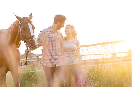 Affectionate couple walking with horse in rural pasture Stock Photo - Premium Royalty-Free, Code: 6113-08220393