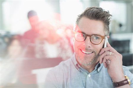Smiling businessman talking on cell phone in office Stock Photo - Premium Royalty-Free, Code: 6113-08220322