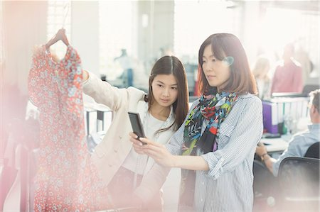Fashion designers photographing dress with camera phone Stock Photo - Premium Royalty-Free, Code: 6113-08220338