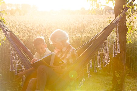 Grandmother and grandson reading book in sunny rural hammock Stock Photo - Premium Royalty-Free, Code: 6113-08220483