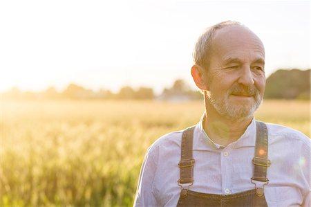 Close up senior farmer in sunny rural wheat field Stock Photo - Premium Royalty-Free, Code: 6113-08220482