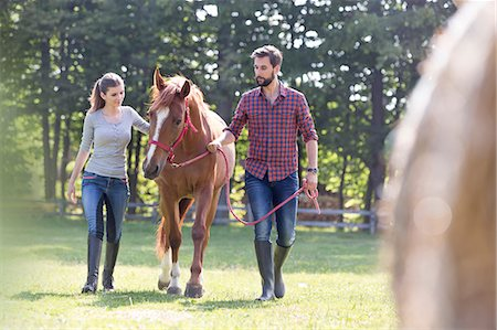 Couple walking horse in rural pasture Stock Photo - Premium Royalty-Free, Code: 6113-08220406